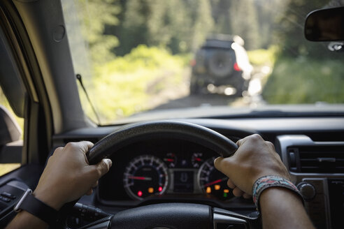 Personal perspective man enjoying overland adventure, driving SUV on forest road - HEROF08753