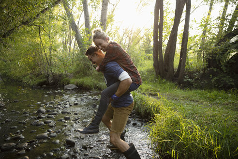 Playful couple piggybacking through stream in woods - HEROF08789