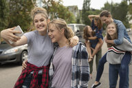 Playful teenagers piggybacking and taking selfie with camera phone on street - HEROF08834