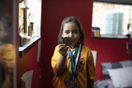 Portrait confident soccer boy in uniform showing medal - HEROF08882