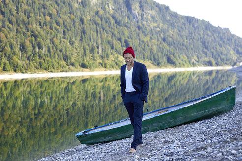 portrait mann mit roter mütze und anzug outdoor am see mit boot - PNEF01196