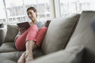 Woman with digital tablet on sofa - HEROF09001