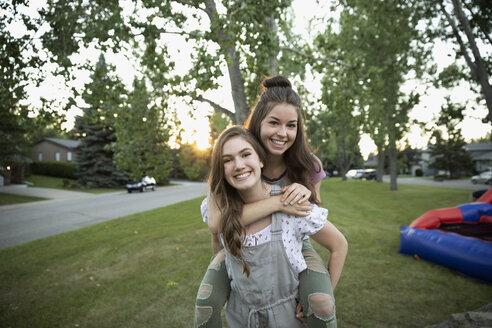 Portrait playful teenage girl friends piggybacking in park - HEROF09133