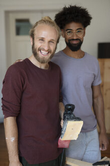 Portrait smiling gay male couple with sander, doing DIY carpentry project - HEROF09148
