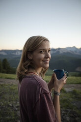 Portrait smiling, carefree woman drinking coffee in field, Alberta, Canada - HEROF09154