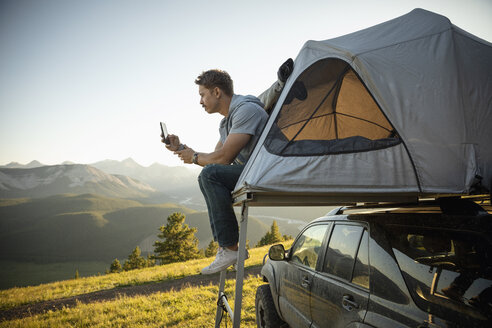 Serene man camping, relaxing at SUV rooftop tent in sunny, idyllic field, Alberta, Canada - HEROF09157