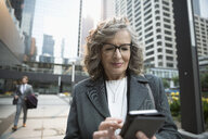 Senior businesswoman using smart phone on city sidewalk - HEROF09169