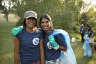 Portrait smiling mother and daughter volunteering, cleaning up garbage in park - HEROF09181