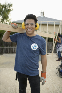 Portrait smiling, confident young male volunteer carrying wood plank, helping build house - HEROF09190