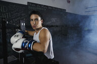 Portrait tough female boxer standing in boxing ring - HEROF09295