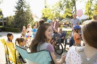 Smiling young woman enjoying summer neighborhood block party in park - HEROF09316