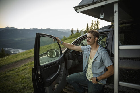 Thoughtful man at SUV on remote mountain hilltop, Alberta, Canada - HEROF09340