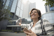 Smiling senior businesswoman hailing taxi on urban sidewalk - HEROF09358