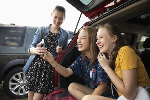 Teenage girls taking selfie at back of car - HEROF09376