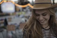 Smiling young woman in hat at movie in the park - HEROF09439