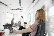 Thoughtful businesswoman with feet up at laptop in office - HEROF09457