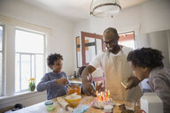 Father and children preparing birthday cake - HEROF09514