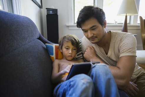 Father and son using digital tablet on sofa - HEROF09517