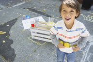 Portrait of enthusiastic boy holding lemons in shirt - HEROF09571