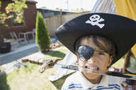 Portrait of boy in pirate hat biting sword - HEROF09574