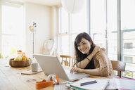 Smiling woman using laptop at table - HEROF09580