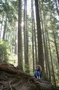 Woman writing in journal against tree in woods - HEROF09604