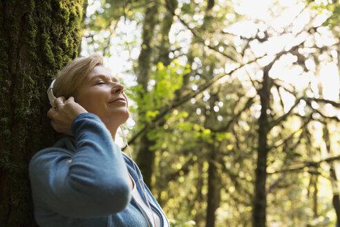 Serene woman listening to music in woods - HEROF09646