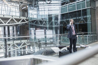 Businessman talking on cell phone in airport atrium - HEROF09694