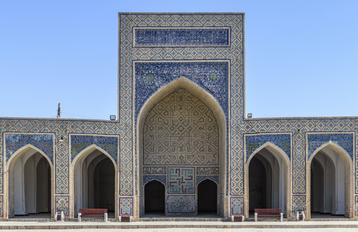 Madrasa facade with a tall arch and blue ceramic glazed tiles, decorated walls and a colonnade in Bukhara. - MINF10118