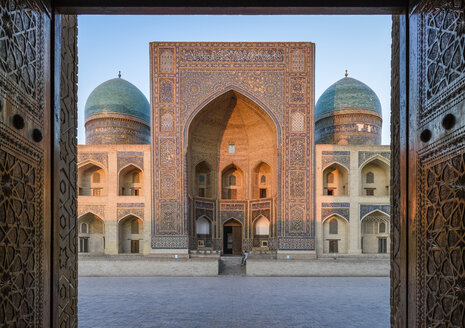 View into the courtyard and the decorated arch and minarets of a Madrasa or mosque in Bukhara city centre. - MINF10121