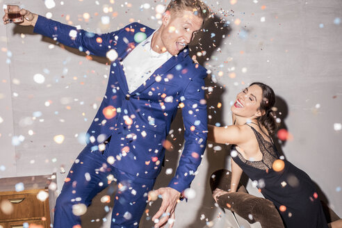 junges paar in konfetti regen auf party, studio, münchen, deutschland - PNEF01203