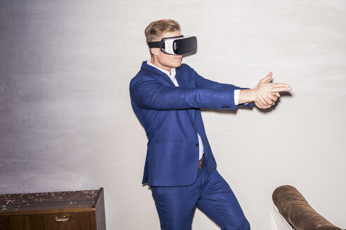 Young man wearing blue suit using Virtual Reality Glasses - PNEF01209