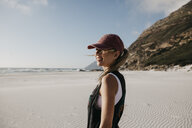 South Africa, Western Cape, Noordhoek Beach, smiling young woman wearing base cap standing on the beach - LHPF00402