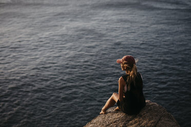 South Africa, Western Cape, woman sitting on a rock watching sunset, seen from Chapman's Peak Drive - LHPF00411