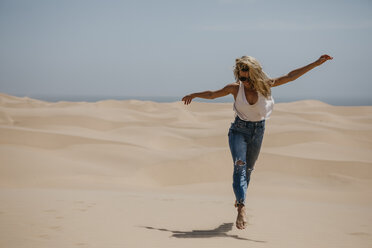 Namibia, Walvis Bay, Namib-Naukluft National Park, Sandwich Harbour, happy woman in dune landscape - LHPF00432