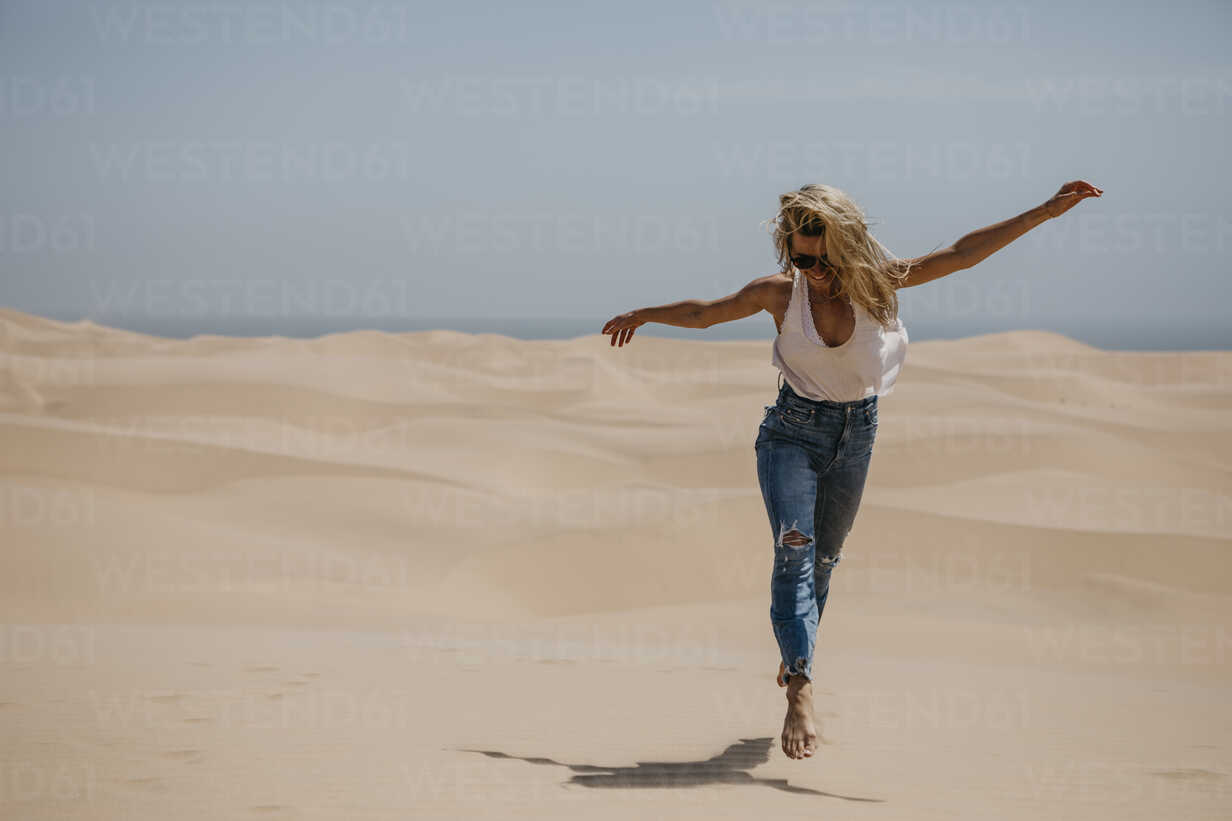 Namibia, Walvis Bay, Namib-Naukluft National Park, Sandwich Harbour, happy woman in dune landscape - LHPF00432 - letizia haessig photography/Westend61