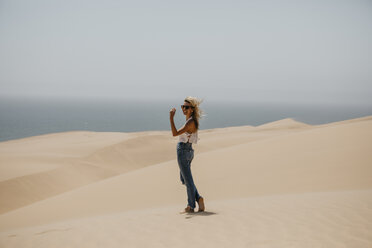 Namibia, Walvis Bay, Namib-Naukluft National Park, Sandwich Harbour, happy woman in dune landscape - LHPF00435