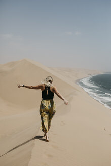 Namibia, Walvis Bay, Namib-Naukluft National Park, Sandwich Harbour, woman walking in dune landscape at the sea - LHPF00438