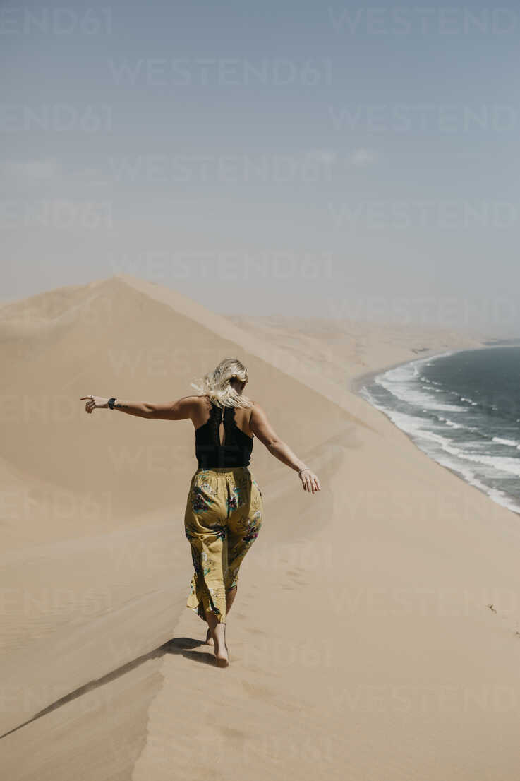 Namibia, Walvis Bay, Namib-Naukluft National Park, Sandwich Harbour, woman walking in dune landscape at the sea - LHPF00438 - letizia haessig photography/Westend61