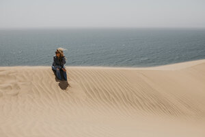 Namibia, Walvis Bay, Namib-Naukluft National Park, Sandwich Harbour, woman sitting in dune landscape at the sea - LHPF00441
