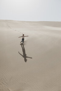 Namibia, Walvis Bay, Namib-Naukluft National Park, Sandwich Harbour, woman running in dune landscape - LHPF00444