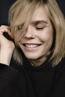 Portrait of smiling blond young woman wearing black pullover - JESF00213