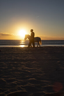 Spain, Tarifa, man walking with pony on the beach at sunset - KBF00482