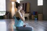 Woman meditating in lotus position with hands clasped - HEROF09812