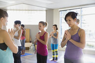 Women with hands at heart center yoga class - HEROF09830