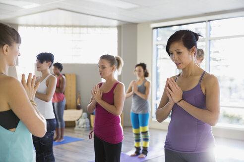 Women with hands at heart center yoga class - HEROF09830