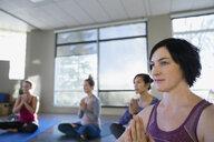 Women with hands at heart center yoga class - HEROF09857