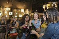 Smiling women toasting beer bottles at bar - HEROF09890