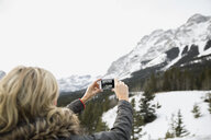 Woman photographing snowy mountains - HEROF09917