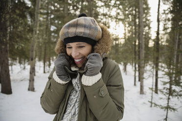 Smiling woman wearing warm clothing in snowy woods - HEROF09920